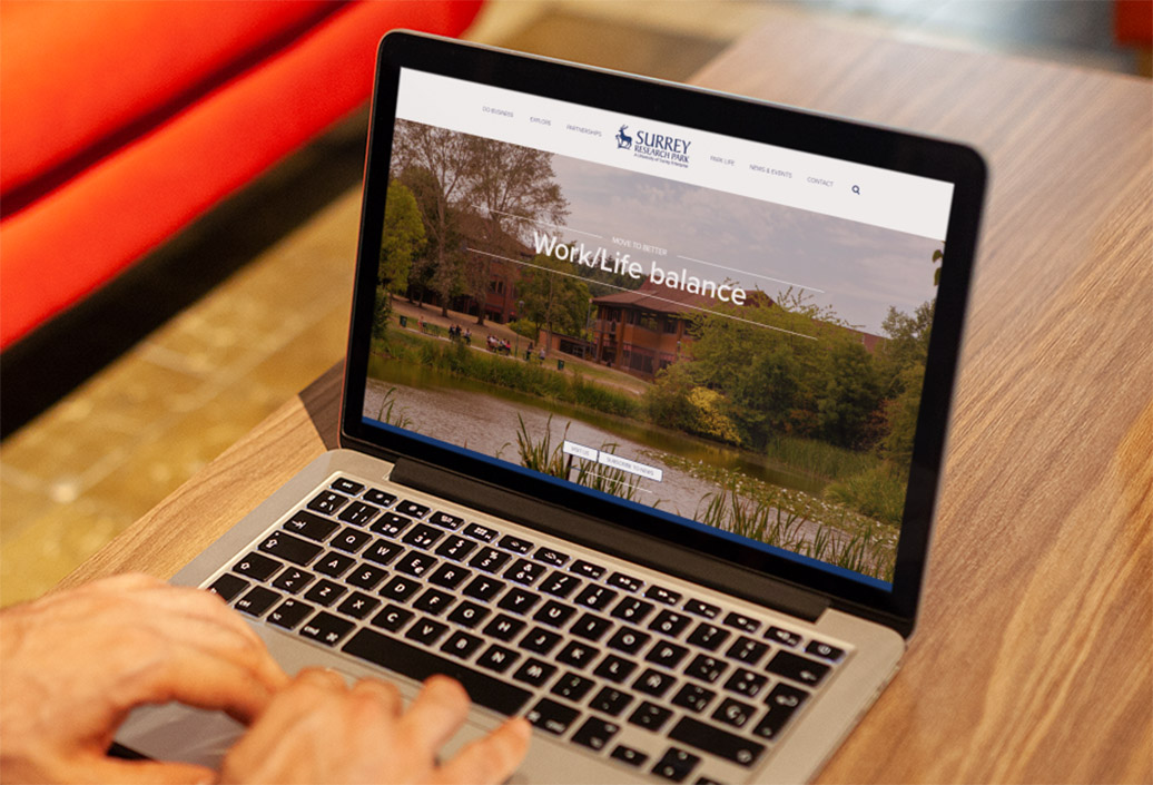 Surrey Research Park website landing page viewed on a laptop with scenes of the park surroundings across a lake